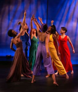 Six women dance against a purple and blue background, wearing sold colored jumpsuits