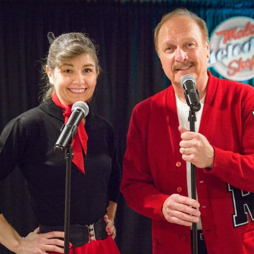 Man and woman in 1950's costumes pose with microphones