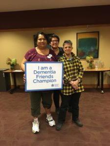 "Three women stand together, smiling. They hold a sign that says ""I am a Dementia Friends Champion."""