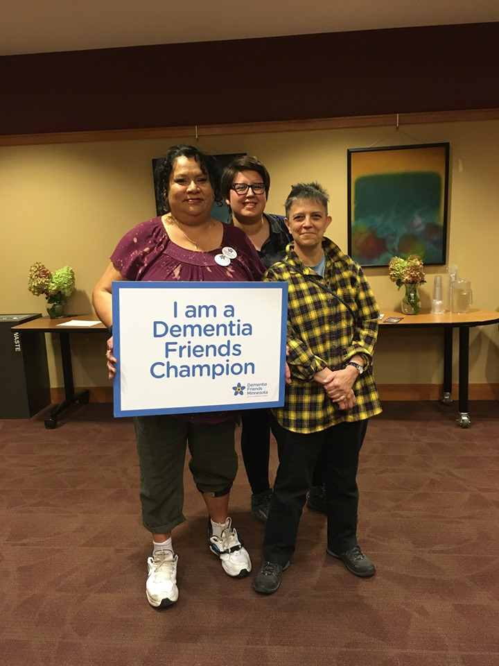 """Three women stand together, smiling. They hold a sign that says """"I am a Dementia Friends Champion."""""""