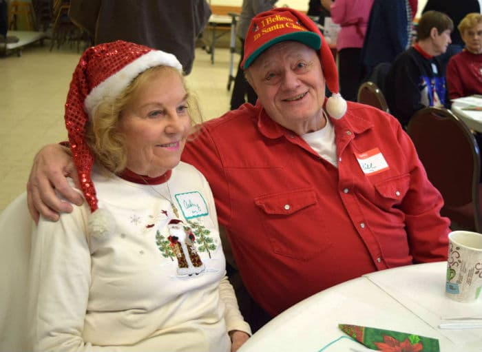 Man and woman dressed for a holiday party. They wear santa hats.