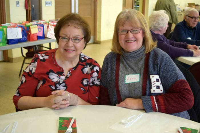 Two woman in holiday themed sweaters smile for the camera