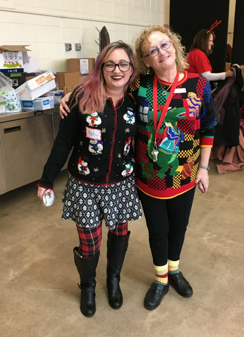 Two people in holiday themed outfits smile for the camera