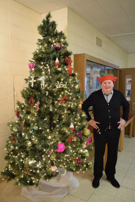 A man in an elf hat stands next to a Christmas tree