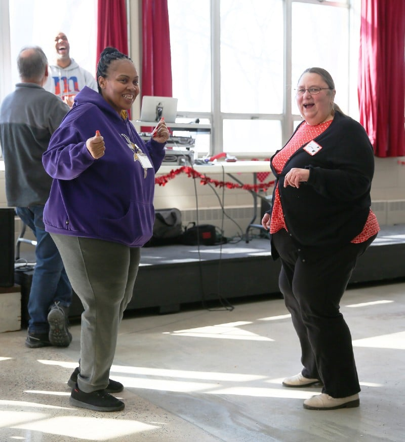 Two women dance, smiling for the camera
