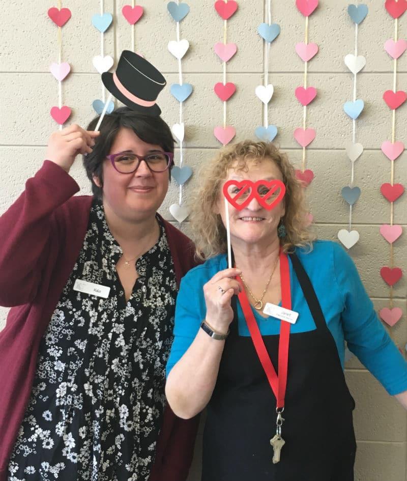 Two women pose in front of a heart wall