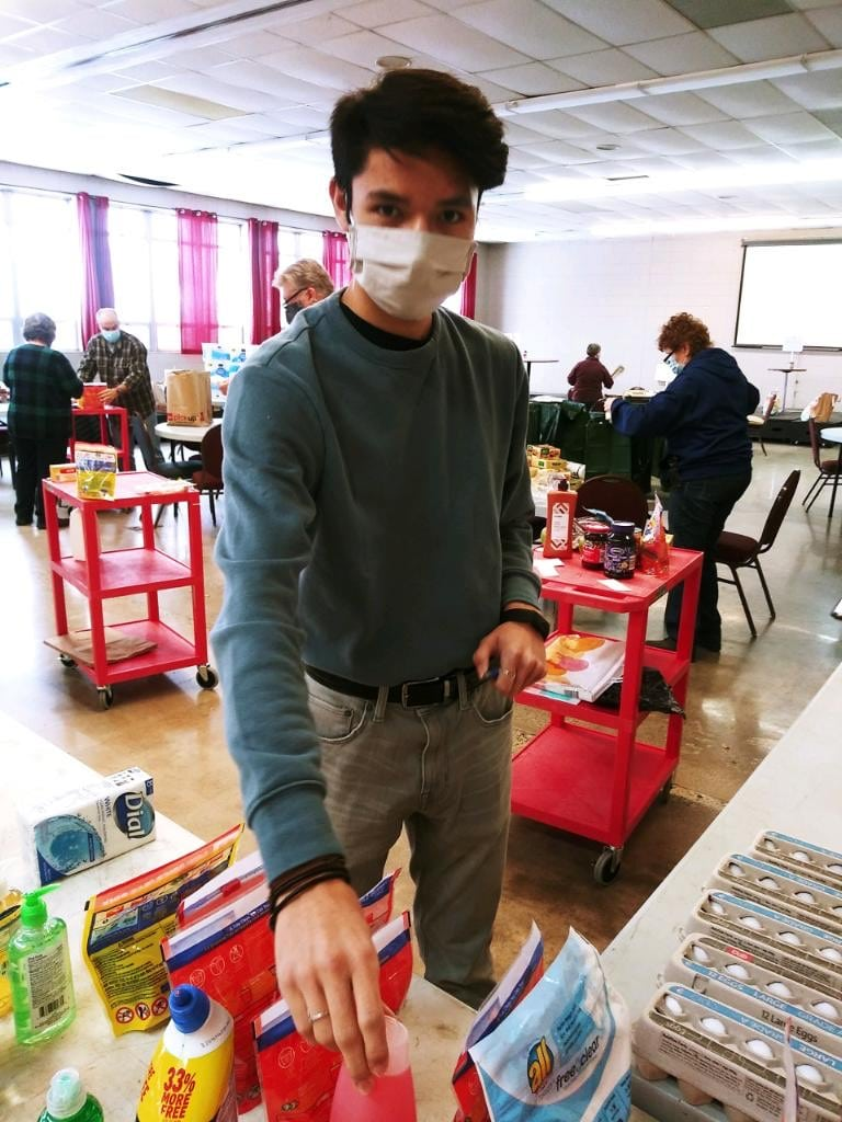 Volunteer wearing a face mask helps pack food for seniors.