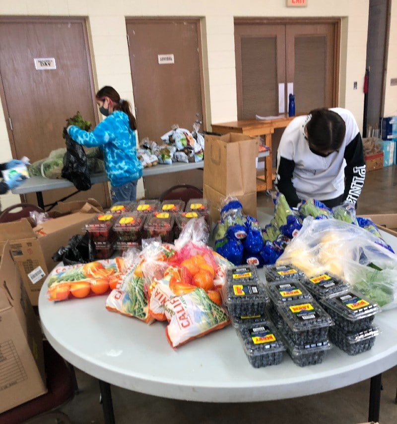 Image of volunteers packing food into bags for delivery.